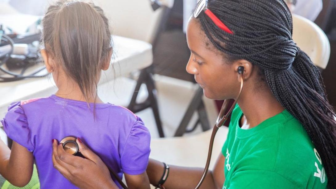 A Medicine volunteer measures a child's heart rate as part of one of our best volunteer abroad programmes.